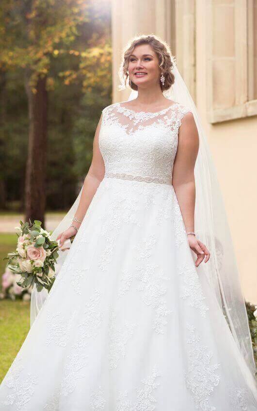01101c768cc This traditional plus size ballgown wedding dress from Stella York features  lace over tulle in a soft A-line silhouette